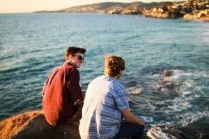 two men talking on the beach