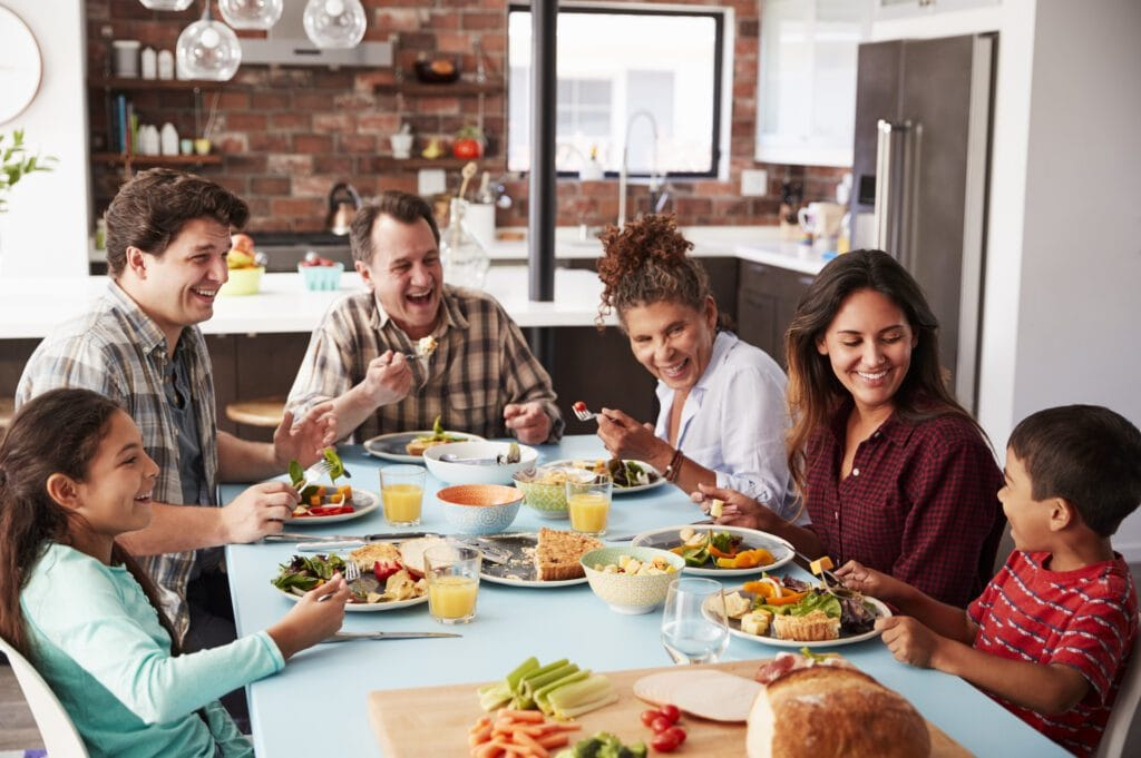 Multi Generation Family Enjoying Meal Around Table At Home Together