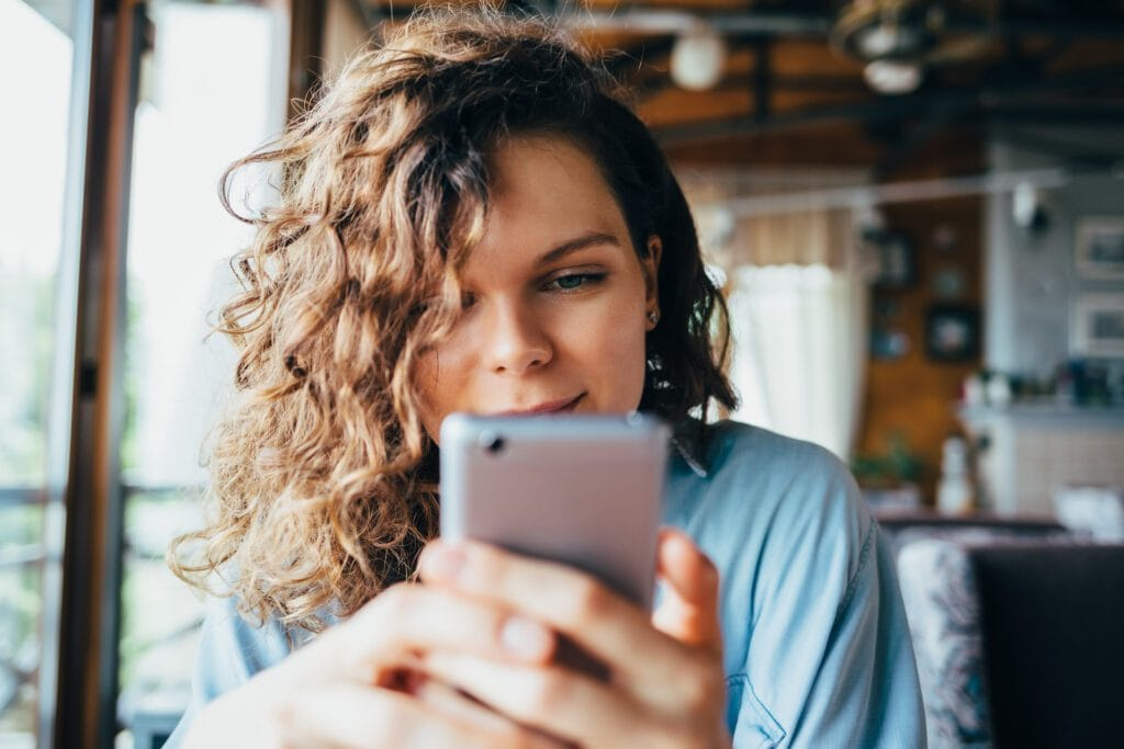 Close-up portrait of young woman texting on phone