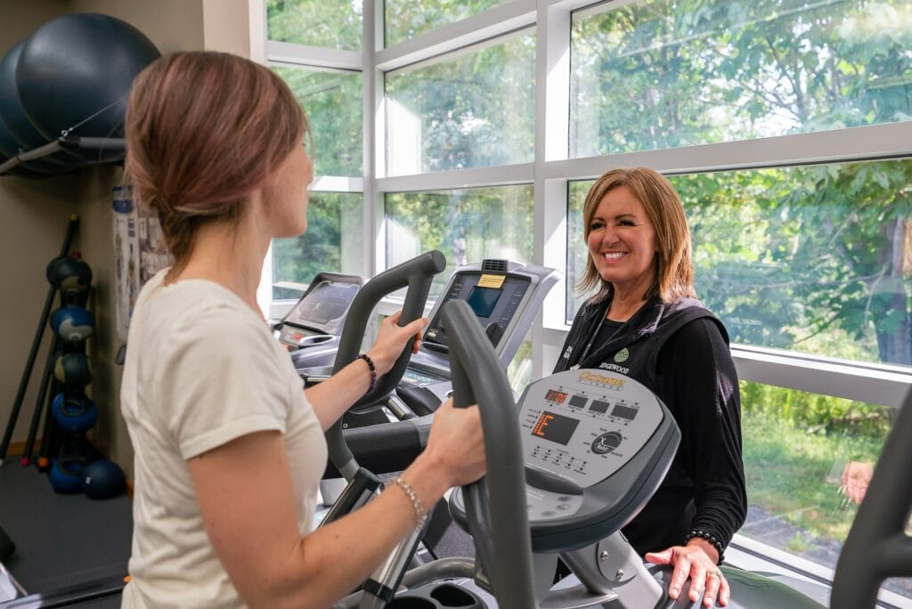 Woman on workout machine being coached