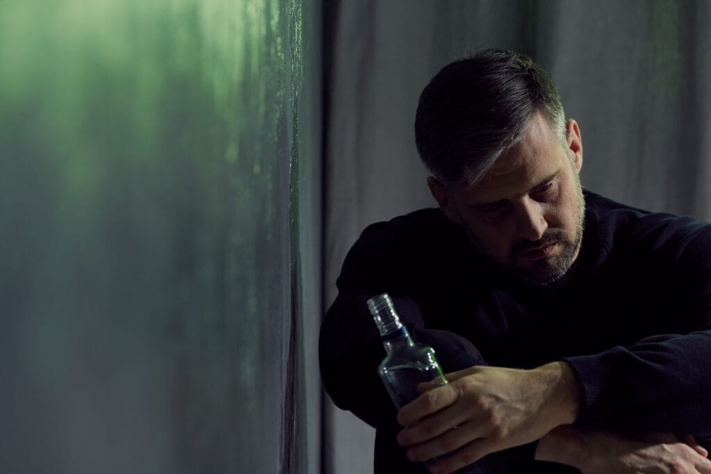 Alcohol addicted man sitting alone with alcohol bottle
