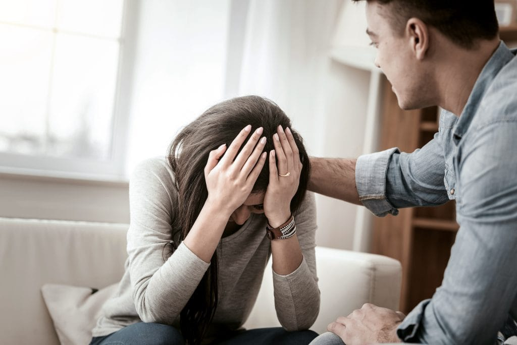 Upset brunette girl touching her head with both hands