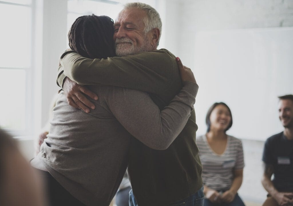 Old man consoling a woman with a hug