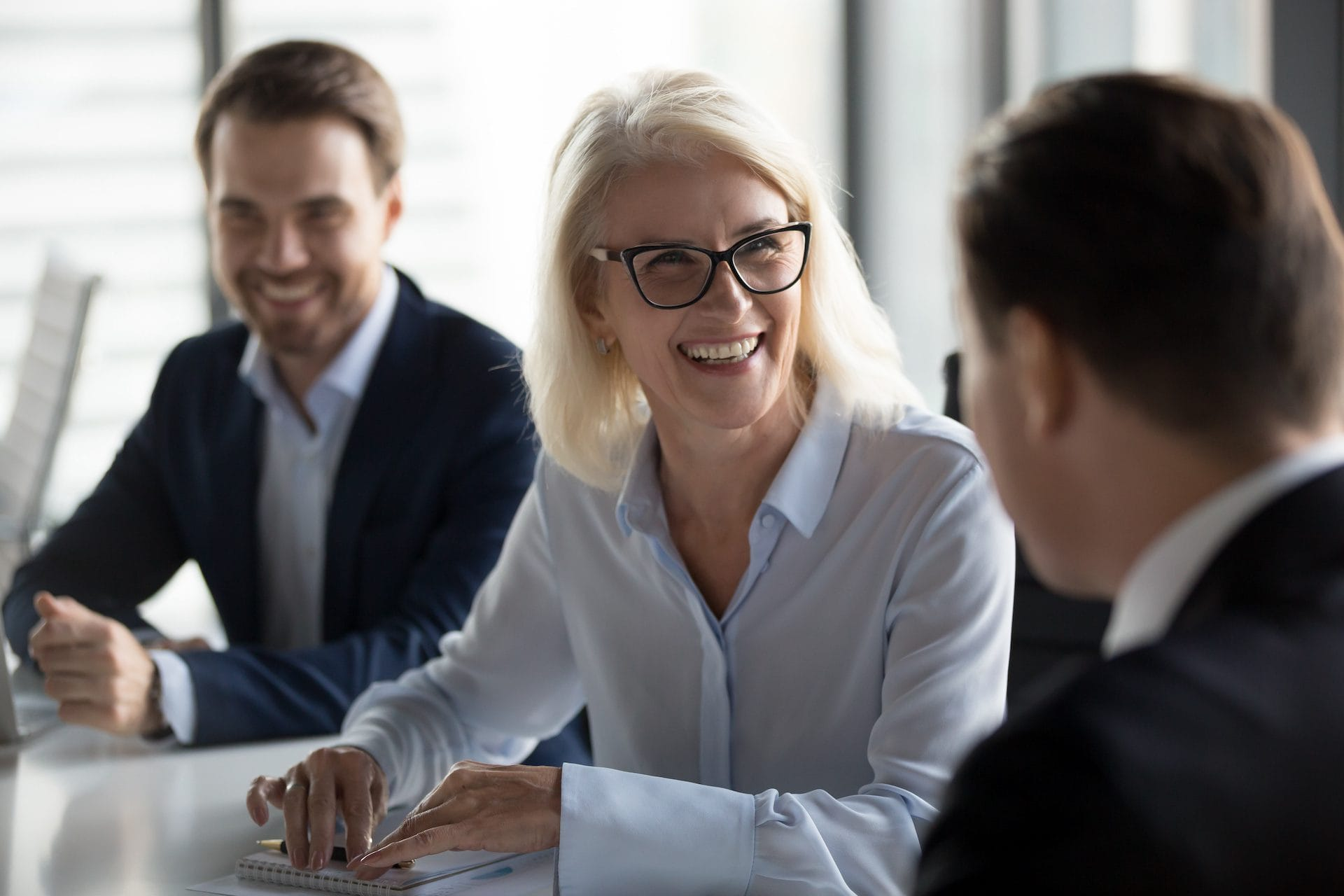 Friendly middle aged female leader laughing at group business meeting