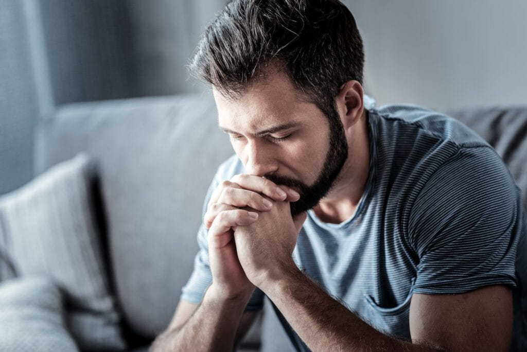 Unhappy man holding his chin and looking down while thinking what to do about his problem