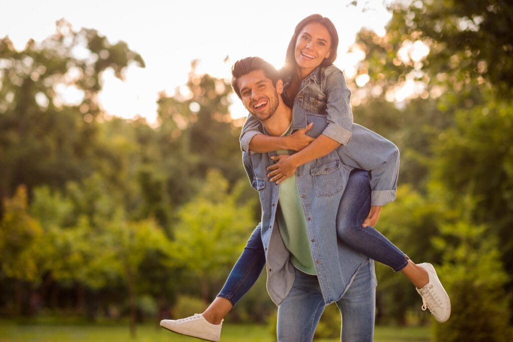 Cheerful spouses with brunet hair piggyback in park outside