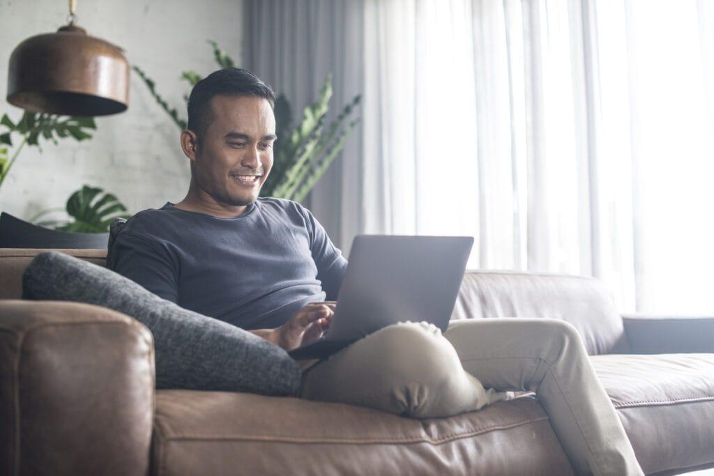 Man looking at the computer at home.